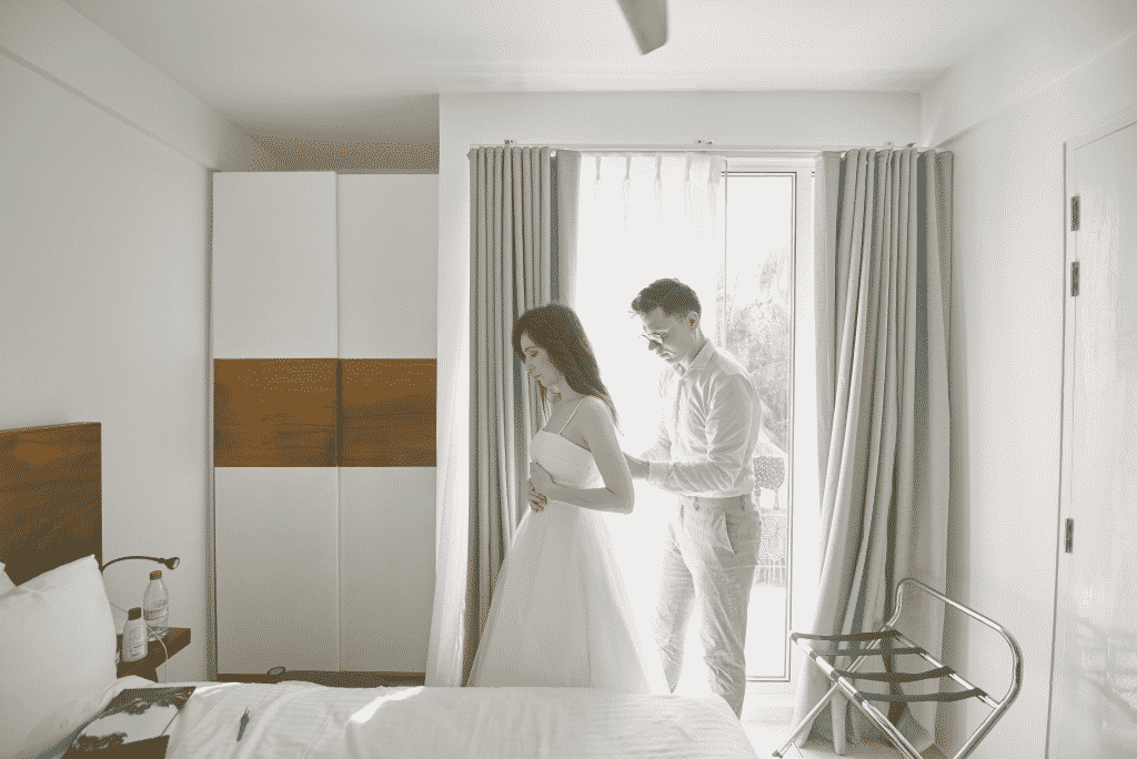 Wedding couple getting dressed in their bedroom