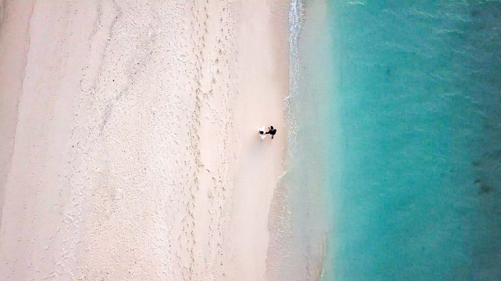 Drone shot of a couple walking on the beach