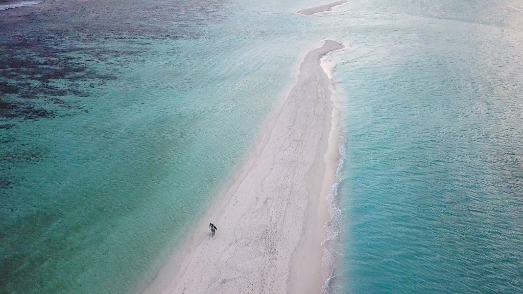 Couple walking on the tip of Dhigurah island