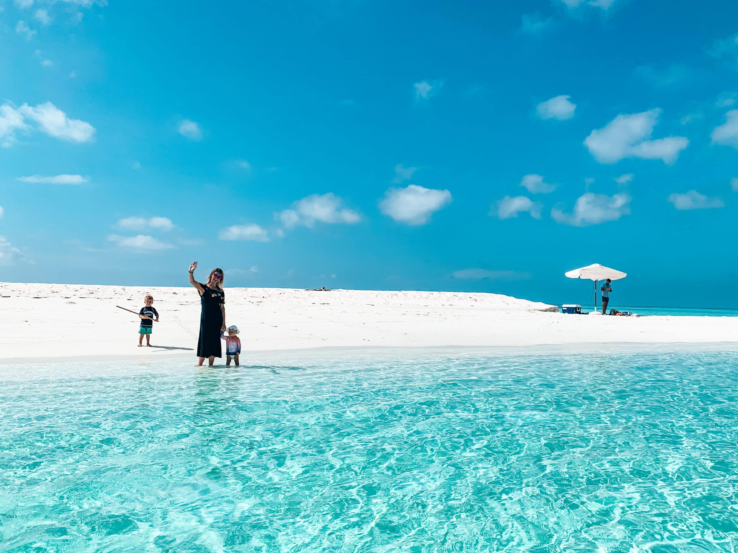 Family Deal - Family waving from a remote sandbank where they'll have a picnic