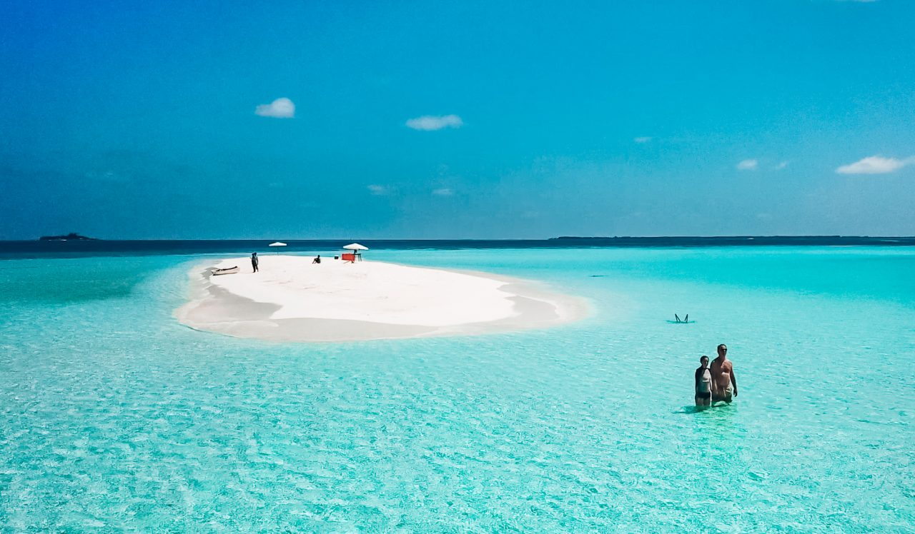 Activities on Dhigurah - Couple standing in the water around their private sandbank where they'll spend the day